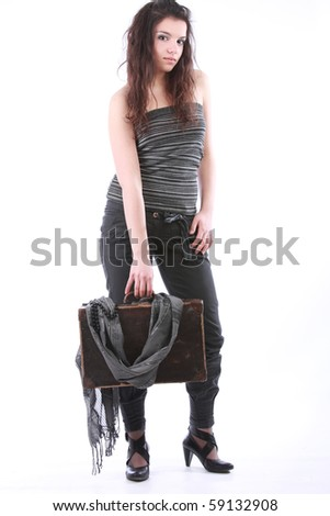 beautiful fashionable girl holding an old suitcase