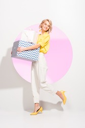beautiful fashionable girl holding gift boxes and smiling on white with pink circle