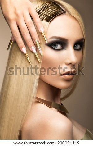 Beautiful fashionable girl in a glamorous image with bright makeup and long gold nails. Art design manicure.