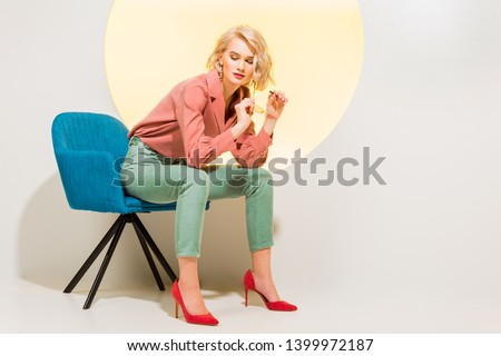 beautiful fashionable girl in colorful clothes sitting in armchair on white with yellow circle and copy space #1399972187