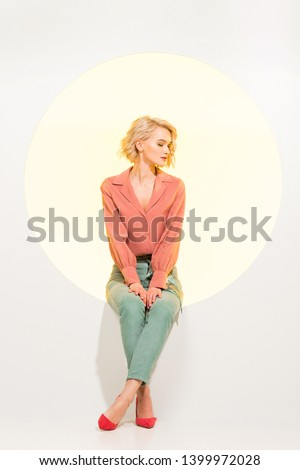 beautiful fashionable girl posing while sitting on yellow circle with white background