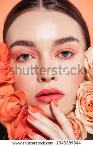 beautiful fashionable girl posing with rose flowers isolated on coral #1343389844