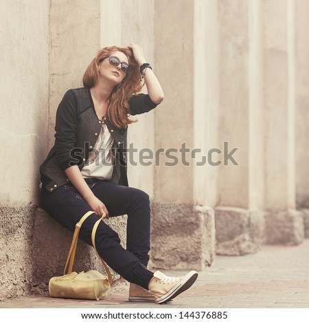 Beautiful fashionable girl sitting in sunglasses with a bag