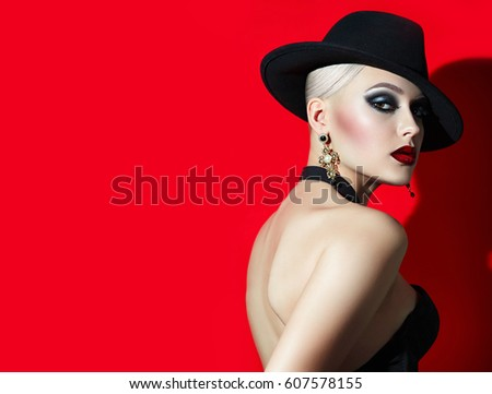 Stock Photo Beautiful fashionable girl with blonde hair rock in a black hat with red lips, eyes smokeys. Girl in the studio on a red background. photoshoot . Advertising cosmetics.  Photostudio. jewelry jewelry.