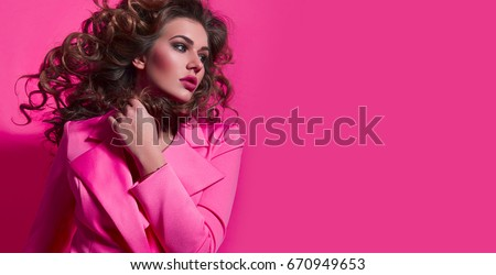Beautiful fashionable girl with long curly hair in a pink jacket. Girl in the studio on a pink background.Advertising, hair products, beauty salon, cosmetics, clothing. Fashion, boutique. Pink.