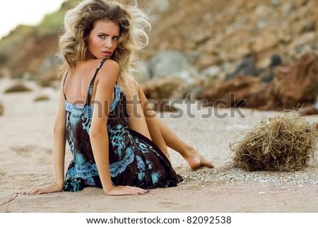 Beautiful fashionable model on the beach in beautiful dress