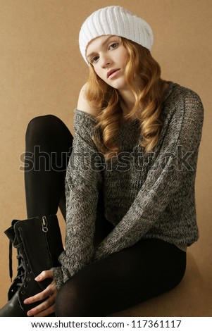 beautiful fashionable model with curly hair in white hat on cube over wooden background. studio shot. daylight