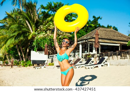 Beautiful fashionable sexy cute happy girl running on the beach with a yellow rubber ring in the hands on the background of the hotel, trendy turquoise swimsuit, sunglasses, hairstyle with horns
