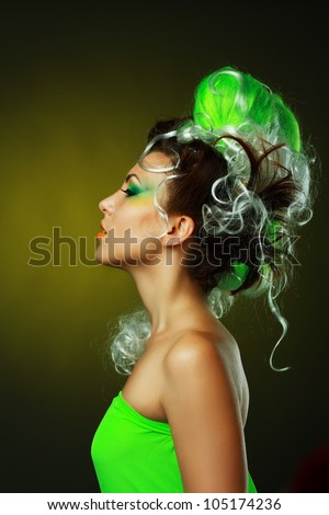 beautiful fashionable smiling young woman with creative hairstyle with green false hairs and art make up