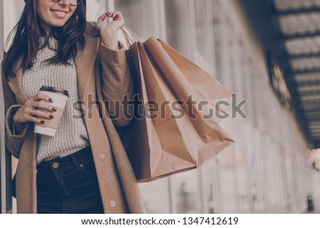 Beautiful fashionable woman drink coffee walking near mall with shopping bags. #1347412619