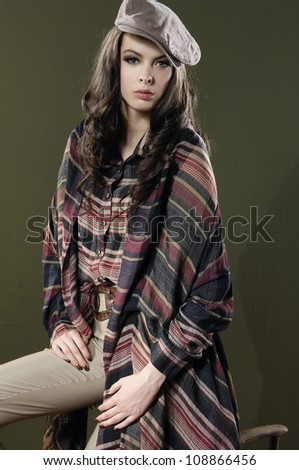 beautiful fashionable woman leaning on a chair