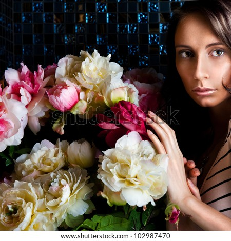 Beautiful fashionable woman portrait indoors at vintage luxury interior. She is standing near bouquet of beautiful flowers