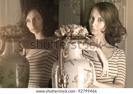 Beautiful fashionable woman portrait indoors at vintage luxury interior. She is standing near vase with roses and huge mirror
