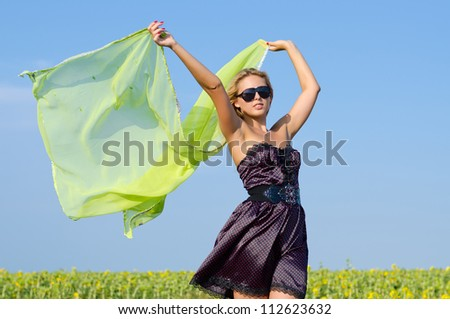 Beautiful fashionable woman standing in a green field against blue sky with a green scarf blowing in the wind