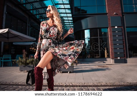 Beautiful fashionable woman walking in the street, wearing sunglasses, nice dress, high heels boots, handbag. Fashion urban autumn photo.