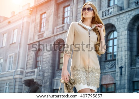 Beautiful fashionable woman walking on the city street. Elegant businesswoman outdoor.