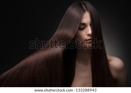 beautiful fashionable woman with long hair on dark background
