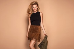 Beautiful fashionable young blonde woman posing in a studio, suede skirt. Long wavy hairstyle. Fashion autumn spring summer photo.