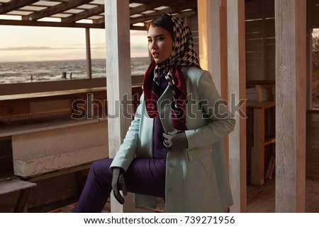 beautiful fashionable young lady posing at sunset on the coast. Model wearing stylish accessories and clothing. Women's beauty and fashion. #739271956