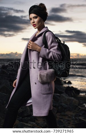 beautiful fashionable young lady posing in the coat in the evening sunset on the Bay. Model wearing stylish accessories and clothing. Women's beauty and fashion. #739271965
