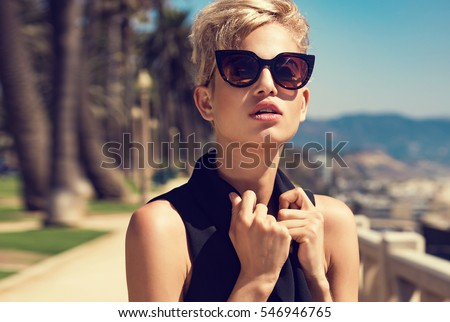 Beautiful fashionable young woman posing in the park, sunglasses, black jumpsuit, high heels, short blonde hair. Fashion summer photo. Bright colors. Nice view #546946765
