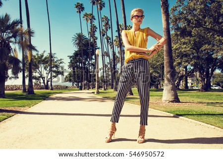 Beautiful fashionable young woman posing in the park, sunglasses, yellow top, high heels, short blonde hair. Fashion summer photo. Bright colors. Nice view