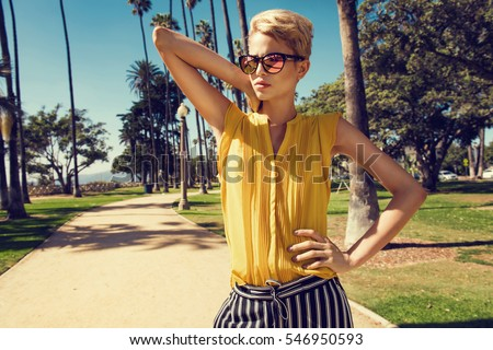Beautiful fashionable young woman posing in the park, sunglasses, yellow top, high heels, short blonde hair. Fashion summer photo. Bright colors. Nice view #546950593