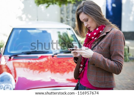 Beautiful fashionable young woman texting on her mobile phone with red car in the background