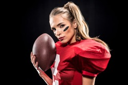 Beautiful female american football player with ball looking at camera isolated on black