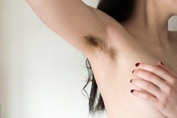 Beautiful female armpits with dark hair. Woman raising her arm and showing unshaven hairy armpits. Bodypositive, feminism and body care concept.