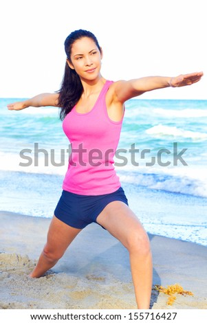 Beautiful female at beach doing yoga warrior pose looking over her right arm for perfect alignment, clearing her mind from the day, stress free