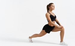Beautiful female athlete stretching before workout indoors. Sport woman stretch legs, doing gym exercises alone isolated white background, silhouette of girl warming up