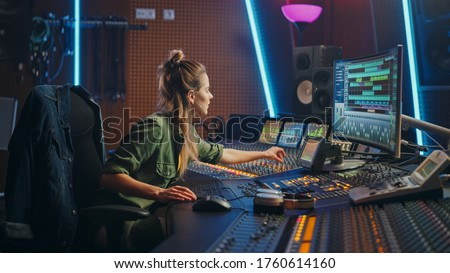 Beautiful Female Audio Engineer Working in Music Recording Studio, Uses Mixing Board and Software to Create Modern Sound. Creative Girl Artist Musician Working on Control Desk to Produce New Song ストックフォト ©