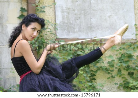 Beautiful female ballet dancer putting on performance shoes