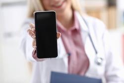 Beautiful female blonde doctor holding smartphone
