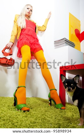 Beautiful female blonde fashion model in bright modern clothing and black dog - little chihuahua