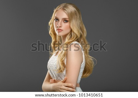 Beautiful female blonde long hair portrait, beauty woman with healthy skin and hair over gray background