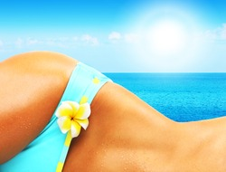 Beautiful female body on the beach, conceptual image of vacation, spa, travel and summertime holidays