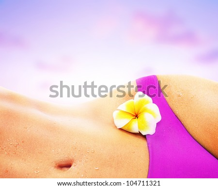 Beautiful female body on the beach, perfect shape slim fit figure, sexy woman over pink sunset sky, girl relaxing in bikini, sunbathing tan skin, conceptual image of vacation, spa and summer holidays
