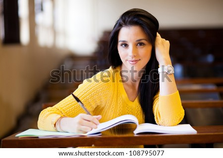 beautiful female college student sitting in classroom