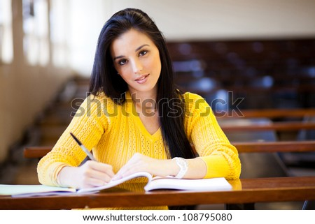 beautiful female college student sitting in lecture hall