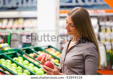 Beautiful female customer selecting apples at supermarket - stock photo