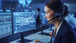 Beautiful Female Data Scientist Works on Personal Computer Wearing a Headset in Big Infrastructure Control and Monitoring Room. Woman Engineer in a Call Center Office Room with Colleagues.