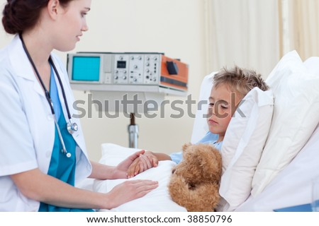 Beautiful female doctor examining a child in bed