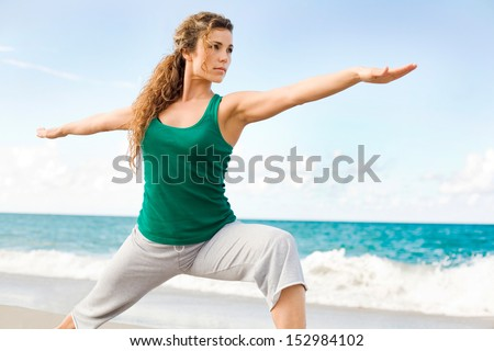 Beautiful female doing yoga warrior pose at the beach with copy space
