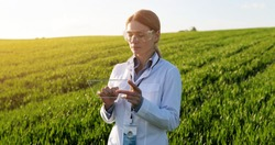 Beautiful female ecologist scientist in goggles standing in green field and working on glass transparent screen. Touchscreen of hi-tech. Scientist with smartphone of future in hands.