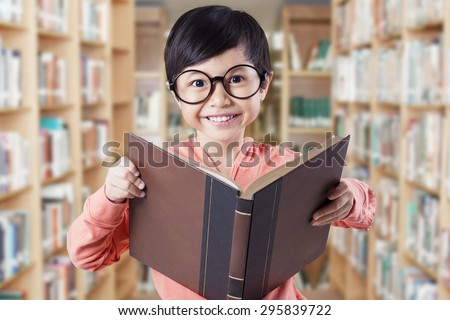 Beautiful female elementary school student standing in the library while wearing glasses and holding a textbook