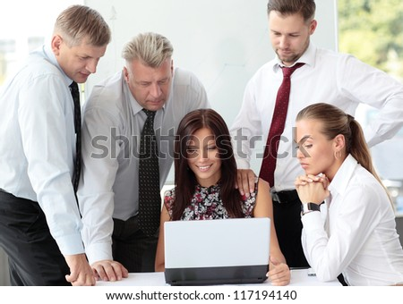 Beautiful female executive pointing at laptop screen while discussing business plan with colleagues
