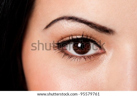 Beautiful female eyebrow and brown eye with lashes on fair skin.