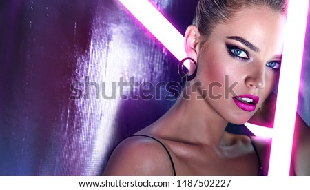 Beautiful female face close-up in neon pink light of bright lamps.Beauty, fashion, silver, sparkles, hairstyle, makeup, glamor, luxury, neon, glow, makeup, bright, model.